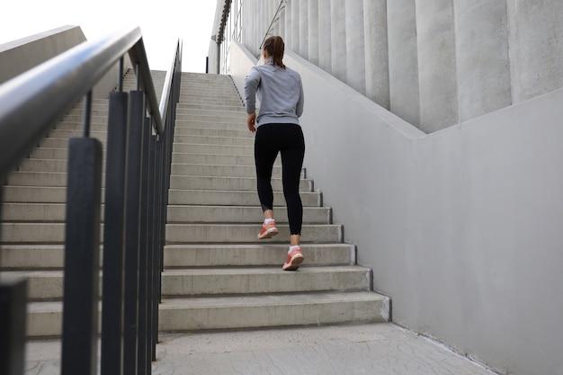 Vue arrière de l'athlète coureur courant dans les escaliers. la forme physique de la femme fait du jogging à l'extérieur.