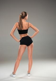 La vue arrière de l'athlète musclé jeune femme posant sur fond gris