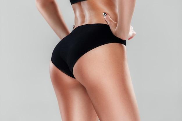 La vue arrière de l'athlète musculaire jeune femme posant sur fond gris studio