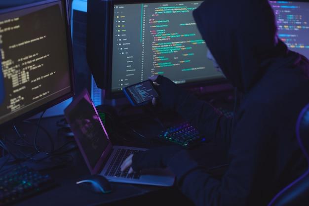 Vue arrière au pirate informatique méconnaissable portant une cagoule tout en travaillant sur la programmation dans une pièce sombre, copiez l'espace