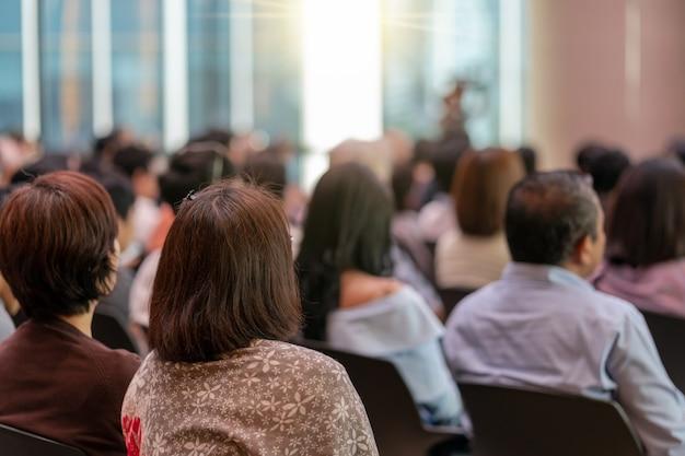 Vue arrière de l'audience dans la salle de conférence ou la réunion de séminaire avec des conférenciers