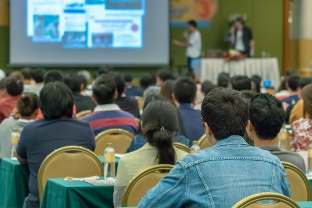 Vue arrière de l'audience écoutant les orateurs présentent la diapositive sur la scène