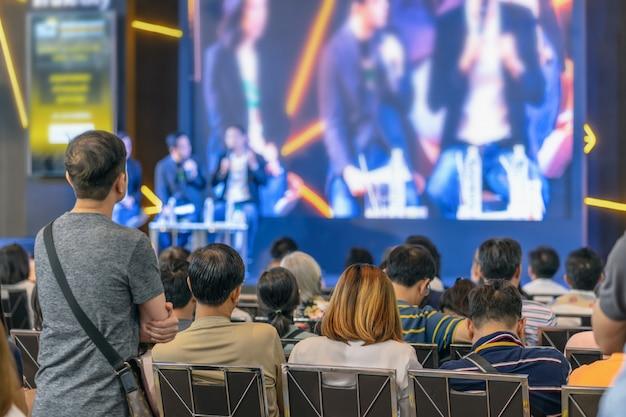 Vue arrière de l'audience à l'écoute des intervenants sur la scène dans la salle de conférence ou une réunion de séminaire