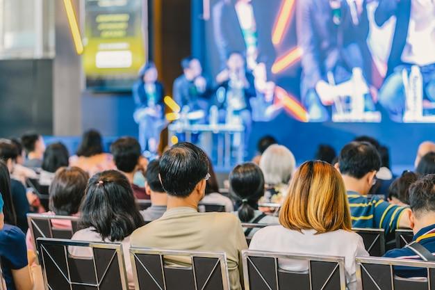 Vue arrière de l'audience à l'écoute des intervenants sur la scène dans la salle de conférence ou un séminaire moi