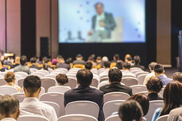 Vue arrière de l'audience à l'écoute des intervenants sur la scène dans la salle de conférence ou de séminaire