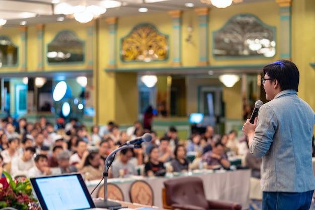 Vue arrière de l'audience montrant la main pour répondre à la question de l'orateur sur la scène