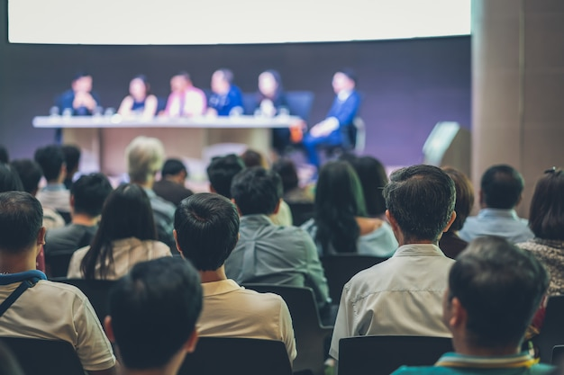 Vue arrière de l'auditoire dans la salle de conférence ou le séminaire avec les cerveaux des orateurs