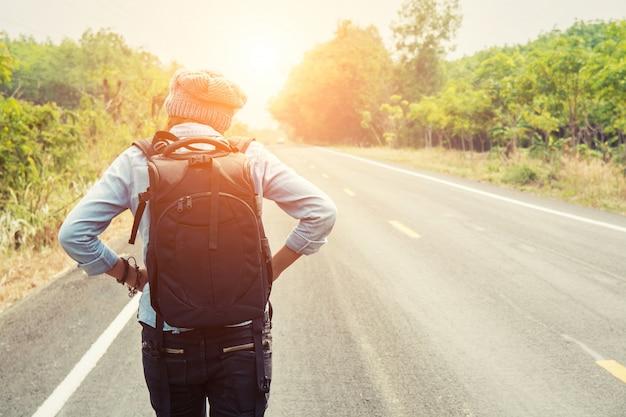 Vue arrière d'aventurier marchant au coucher du soleil