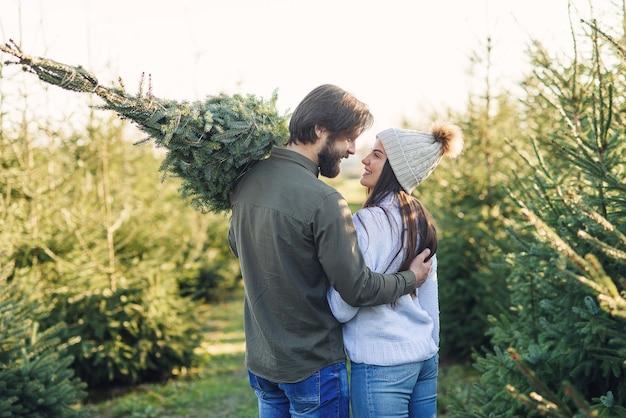 Vue arrière d'un beau jeune couple portant un bel arbre de noël à leur voiture parmi les plantations de sapins.