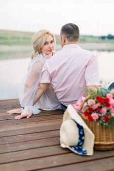 Vue arrière d'un bel homme d'âge moyen et d'une jolie dame blonde charmante, assis ensemble sur le pont en bois au bord du lac ou de l'étang. femme s'appuyant sur son mari et regarde la caméra