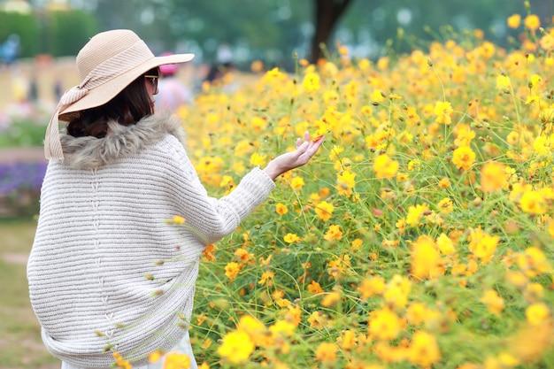 Vue arrière, de, belle, femme asiatique, debout, dans, nature, parmi, cosmos, fleurs, champs, à, paisible