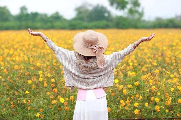 Vue arrière, de, belle, femme asiatique, debout, dans, nature, parmi, cosmos, fleurs, champs, tout, élevé, mains, pacifique