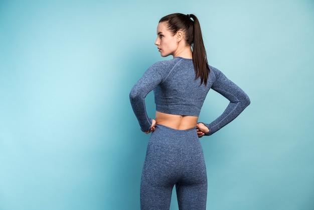 Vue arrière d'une belle femme de remise en forme caucasienne confiante debout après l'exercice isolé sur fond bleu avec espace de copie. concept d'entraînement de fille mince et en bonne santé