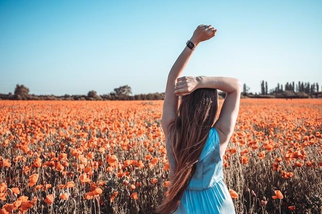 Vue arrière de la belle fille deux mains en l'air sur le pré de coquelicots rouges au coucher du soleil. notion de liberté. couleur vintage.