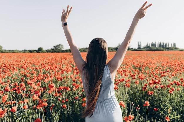 Vue arrière de la belle fille deux mains en l'air sur le pré de coquelicots rouges au coucher du soleil.