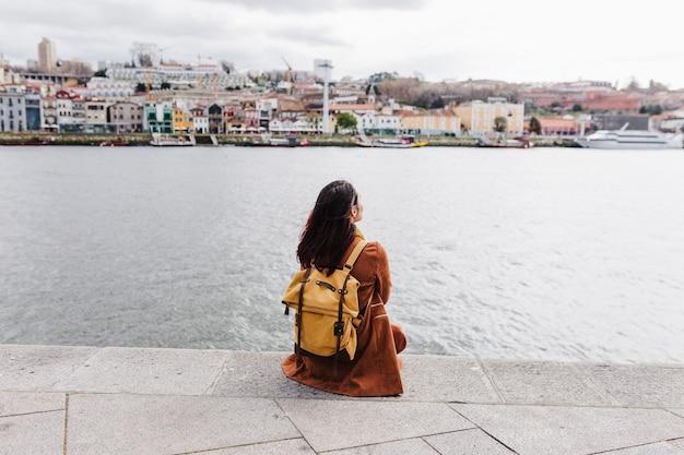 Vue arrière de la belle jeune femme assise au bord de la rivière au coucher du soleil en profitant de la vue sur porto. concept de voyage