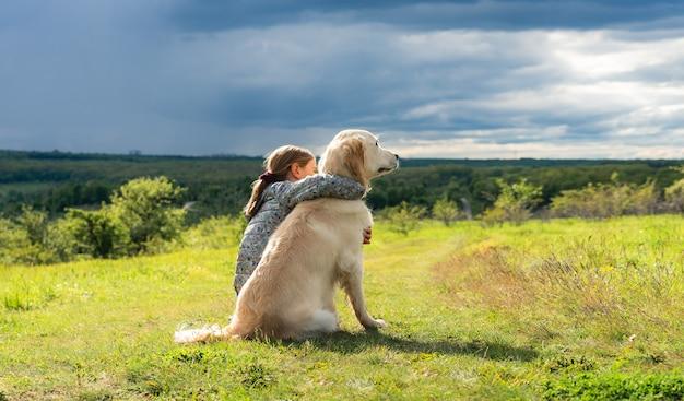 Vue arrière de la belle petite fille embrassant un chien fidèle dans la nature