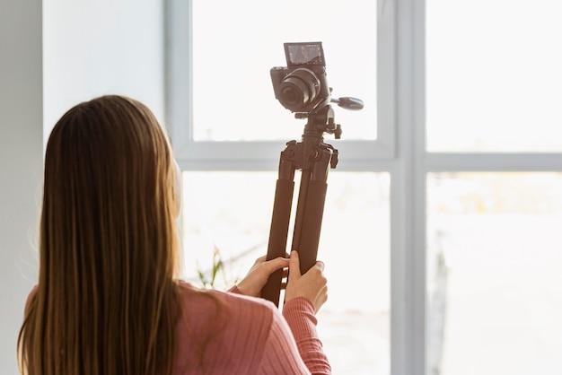 Vue arrière blogueur tenant un trépied avec appareil photo