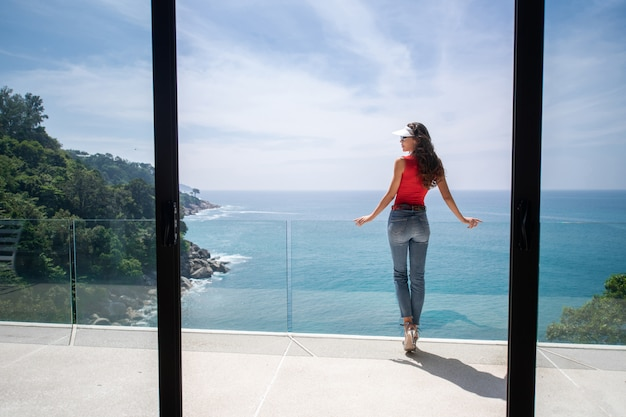 Vue arrière: charmante jeune fille en jeans posant sur un balcon en verre avec une vue magnifique sur la mer. vie luxueuse