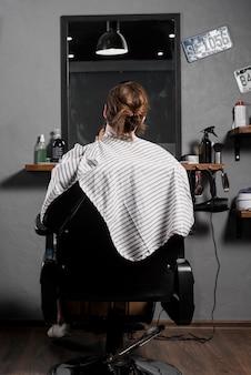 Vue arrière d'un client masculin assis sur un fauteuil dans un salon de coiffure