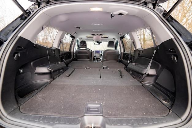 Vue arrière coffre de voiture ouvert avec sièges passagers pliés grand coffre de voiture plat vide gros plan énorme