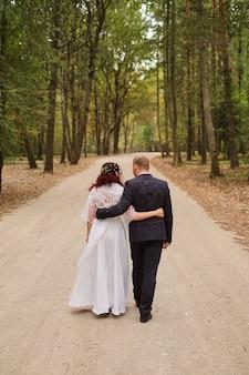 Vue arrière complète des nouveaux mariés marchant le long de la route.