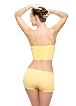 Vue arrière d'un corps féminin parfait avec une taille fine posant isolé sur un mur blanc