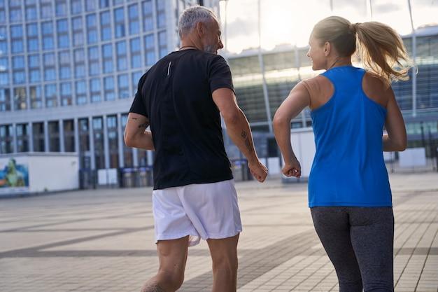Vue arrière d'un couple d'âge moyen en tenue de sport pleine d'énergie faisant du jogging ensemble en milieu urbain