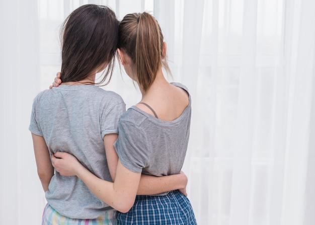 Vue arrière, de, couple lesbien, regarder rideau