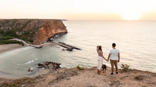 Vue arrière couple regardant le coucher du soleil avec leur chien