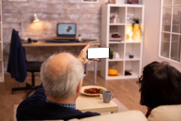 Vue arrière d'un couple de retraités âgés regardant un smartphone avec écran blanc isolé.