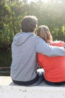 Vue arrière d'un couple romantique en appréciant le coucher du soleil