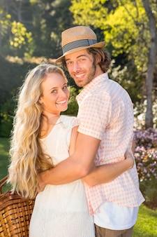 Vue arrière d'un couple tenant un panier de pique-nique dans le jardin