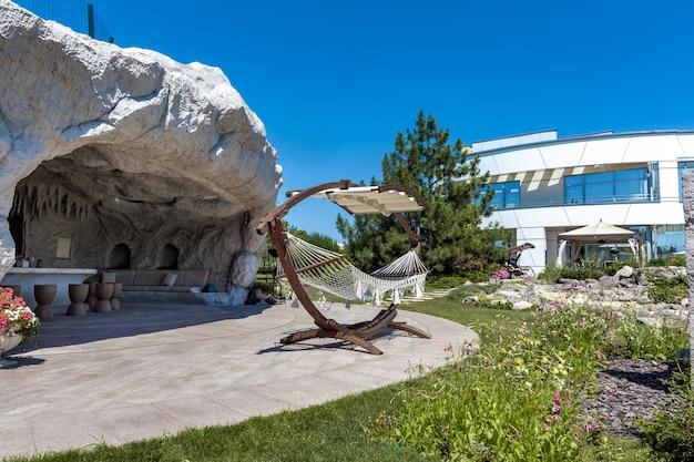 Vue sur l'arrière-cour paysagée du manoir luxueux et du patio équipé d'une grotte en pierre artificielle avec table à manger et hamac avec auvent le jour d'été