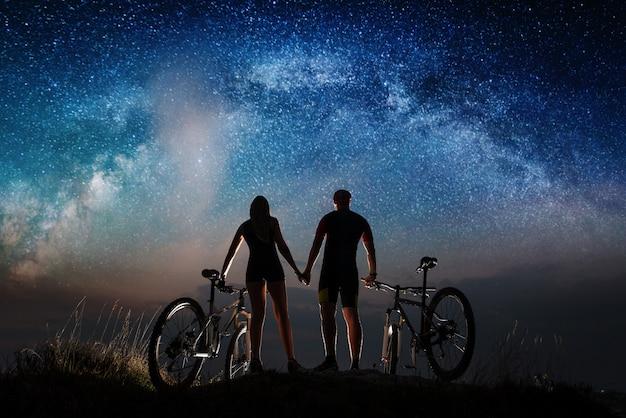 Vue arrière des cyclistes de couple de silhouette tenant par la main, appréciant le ciel étoilé de nuit.