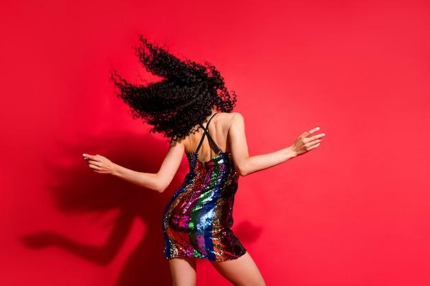 Vue arrière derrière sa magnifique fille aux cheveux ondulés gracieuse dansant isolée sur fond de couleur rouge vif