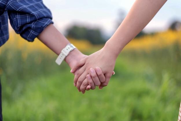 Vue arrière, de, deux adolescents, étudiant, ensemble, tenant main la main