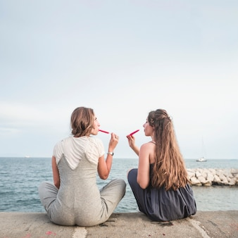 Vue arrière de deux amies assises sur la jetée en train de manger des sucettes rouges