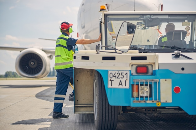 Vue arrière de deux employés masculins de l'aéroport regardant l'avion de ligne atterrir à l'aérodrome