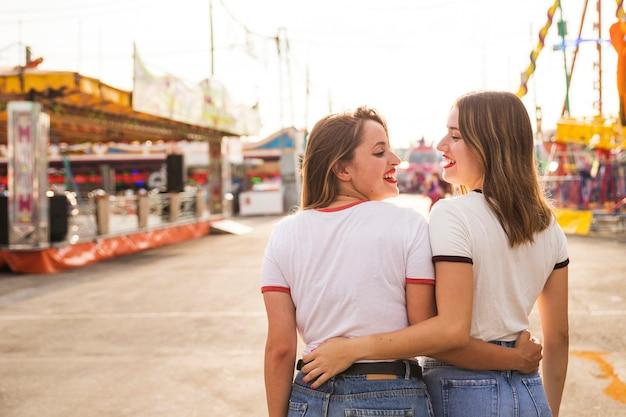 Vue arrière de deux femmes heureuses marchant au parc d'attractions