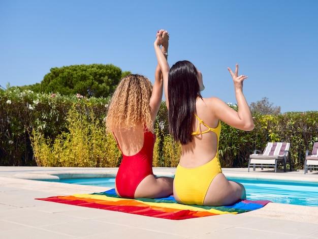 Vue arrière de deux filles célébrant assis sur un drapeau de la fierté gay au bord de la piscine