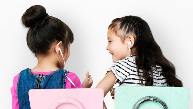 Vue arrière de deux filles écoutant de la musique
