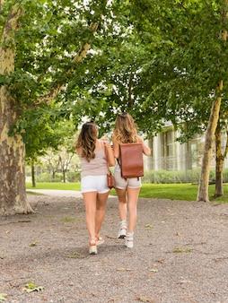 Vue arrière de deux jeunes femmes marchant dans le parc