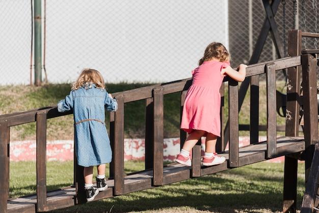 Vue arrière de deux jolies filles jouant sur la promenade