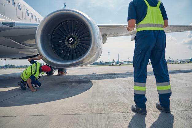Vue arrière de deux mécaniciens professionnels de maintenance d'aéronefs inspectant un moteur d'avion avant le décollage