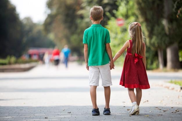 Vue arrière de deux mignons jeunes enfants blonds, fille et garçon, frère et sœur marchant main dans la main sur les arbres verts floues ensoleillées du parc bokeh. concept de relations de frères et sœurs aimants.