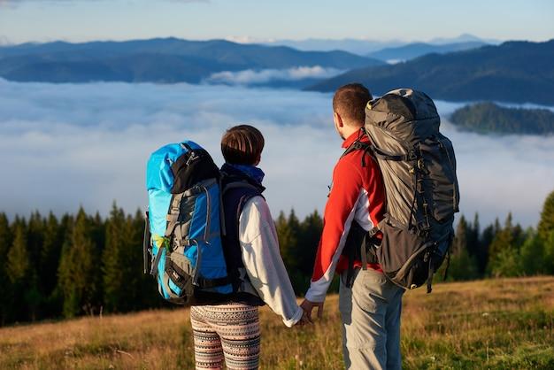 Vue arrière deux personnes se tenant la main profitent du paysage d'une brume dense sur de puissantes montagnes dans les rayons d'un coucher de soleil. fermer