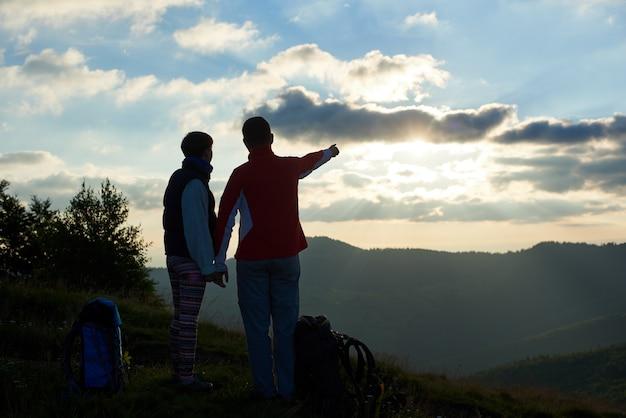 Vue arrière deux touristes sont debout au sommet de la montagne, se tenant la main près de sacs à dos sur fond de montagnes et de ciel nuageux au coucher du soleil. homme montrant sa main au loin