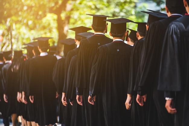 Vue arrière des diplômés se joindre à la cérémonie de remise des diplômes à l'université. graduation de l'éducation dans le concept de thème universitaire.