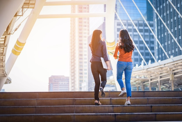 Vue arrière de la diversité des adolescents tenant un ordinateur portable et monter les escaliers aller à une ville